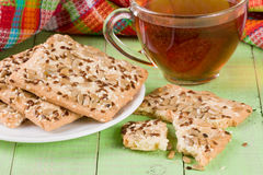Crispy bread with seeds of sunflower, flax and sesame seeds with a cup of tea on a green wooden background Royalty Free Stock Image