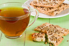 Crispy bread with seeds of sunflower, flax and sesame seeds with a cup of tea on a green wooden background Stock Photo