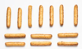 Crispy breadsticks with poppy seeds arranged in rows on a white background royalty free stock photos