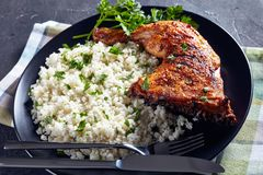 Crispy broiled Chicken Leg Quarter, top view. Crispy broiled Chicken Leg Quarter served with Cauliflower rice or couscous on a black plate on a concrete table stock images