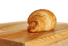 The crispy brown croissant. The crispy croissant on a wooden table royalty free stock images