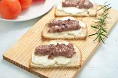 Crispy bruschetta topped with sausage and fresh rosemary Stock Photo