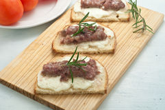 Crispy bruschetta topped with sausage and fresh rosemary Royalty Free Stock Photography