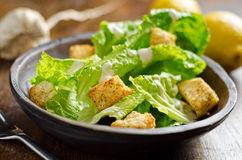 Crispy Caesar Salad. A bowl of crispy caesar salad with croutons, garlic, lemons, and olive oil stock photo