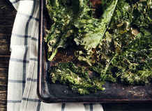 Crispy cheese and chili kale chips on baking tray. Royalty Free Stock Image