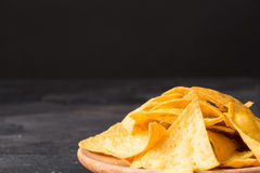 Crispy cheese nachos on a a light wooden round plate. Delicious corn chips on a black background. Copy space. Royalty Free Stock Photos