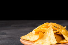 Crispy cheese nachos on a a light wooden round plate. Delicious corn chips on a black background. Copy space. royalty free stock photography