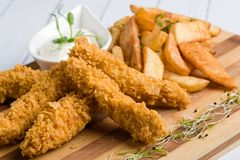 Crispy chicken with fries. Deep fried crispy chicken with fries and dipping sauce royalty free stock image