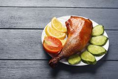 Crispy chicken legs, roasted on a grill with sliced lemon, cucumber and tomatoes on white plate on a wooden table. Copy space royalty free stock photography