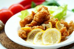 Crispy Chicken with Lemon. Crispy chicken pop served with lemon at famous restaurant Stock Image