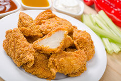 Crispy Chicken Nuggets. A plate of crispy chicken nuggets with celery and peppers and three dipping sauces Stock Photos