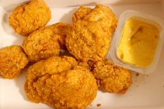 Close up photo of a heap of chicken nuggets  and a plastic container with curry dip sauce. stock photography