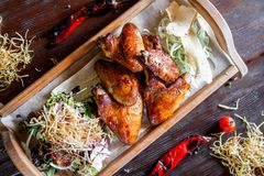 Crispy chicken wings barbecue with peppers and tomatoes on a wooden tray stock photo