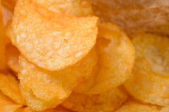 Crispy chips in foreground Royalty Free Stock Photo