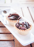 Crispy chocolate tarts on wood table Stock Image