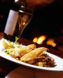 Crispy cod with potato rosti. Two pieces of cooked crispy cod served on top of potato rosti with a bottle and glass of wine in the background Stock Photos