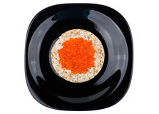 Crispy corn bread with red caviar in black plate Royalty Free Stock Photos