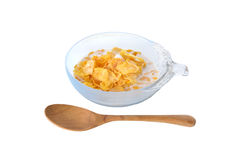 Crispy corn flakes with milk in bowl and wooden spoon on white Stock Images
