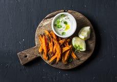 Crispy cornmeal sweet potato fries rustic wooden cutting board on dark background Stock Photography