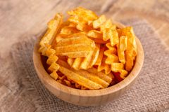 Crispy corrugated potato chips in wooden bowl on burlap napkin. Wooden background. Junk food. Copy space royalty free stock image