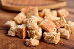 Crispy croutons bread on wooden background stock photography