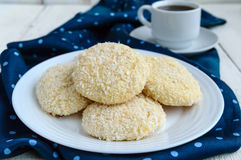 Crispy dietary coconut cookies on a plate and a cup of coffee on a white wooden background. Royalty Free Stock Image