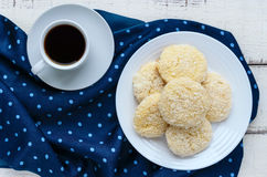 Crispy dietary coconut cookies on a plate and a cup of coffee on a white wooden background. Royalty Free Stock Photo