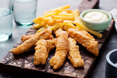 Crispy Fish and Chips, Tartar Sauce. British food. Crispy Fish and Chips with Tartar Sauce Traditional British food on a wooden board Royalty Free Stock Image