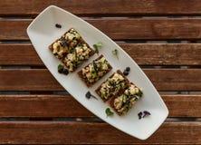 Crispy flatbread sandwitches z sałatkową podprawą słuzyć na białym ceramicznym owalu talerzu na slatted tabletop Zdjęcia Stock