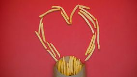 Crispy french fries heart shape symbol on red background, fast food, charity. Stock photo stock photo