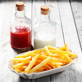 Crispy French Fries on Plate and Sauces in Bottles Royalty Free Stock Image