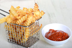 Crispy French Fries in a wire fryer basket with Ketchup Stock Photos