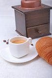 Crispy fresh croissants, cup of coffee espresso and coffee grinder on a white background, morning breakfast, selective Stock Images
