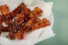Crispy fried bacon rashers draining on plate with napkin on pastel mint green background royalty free stock image