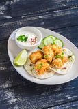 Crispy fried fish on a homemade tortilla. On a dark wooden background Royalty Free Stock Photos