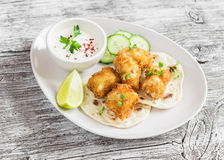 Crispy fried fish on a homemade tortilla. On a light  rustic wooden background Stock Photography