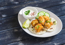 Crispy fried fish on a homemade tortilla on a wooden background. Crispy fried fish on a homemade tortilla on a dark wooden background Stock Photo