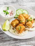 Crispy fried fish on a homemade tortilla on a  wooden background. Crispy fried fish on a homemade tortilla on a light wooden background Royalty Free Stock Photography