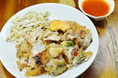 Crispy fried mussel and squid omelet with bean sprout dipping chili sauce on wooden table Stock Images