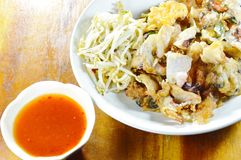 Crispy fried mussel and squid omelet with bean sprout dipping chili sauce on wooden table Stock Image