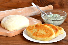 Crispy fried pies on a white plate and on wooden table. Dough and rolling pin on a cutting board. Cottage cheese with green dill Stock Photos