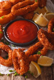 Crispy fried squid rings with ketchup and lemon close-up. vertic Stock Images