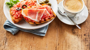 Crispy fried tostada with salsa and ham. Crispy fried tostada topped with fresh tomato and onion salsa and thinly sliced prosciutto ham served with a cup of hot stock photography