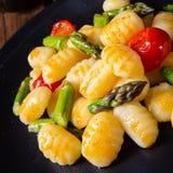 Crispy gnocchi z piec pomidorami i asparagusem obrazy stock