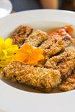 Golden deep fried eggplant with edible flower Royalty Free Stock Image