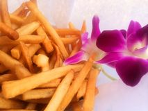 Crispy golden fresh French fries with purple orchid. Snack fries tropical twist American favorite hawaii food garnish crisp golden Stock Images