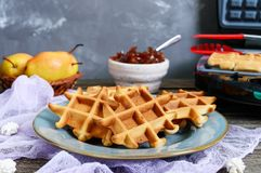 Crispy golden vanilla wafers with pear jam, electric wafer dish. On a wooden background royalty free stock photography