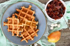 Crispy golden vanilla waffles with pear jam on a wooden background. Top view royalty free stock photo