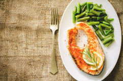 Crispy grilled salmon steak with green beans. On a dark background. toning. selective focus on lemon and rosemary Royalty Free Stock Image