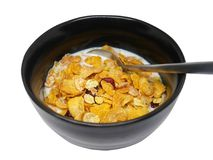 Crispy and healthy organic breakfast cereal flakes with red dried cranberry and cold soy milk in dark black handmade pottery bowl. Spoon on bowl. Isolated on royalty free stock images